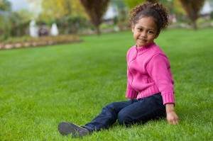 Little girl sitting on lawn